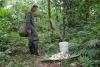 09 Francesco staat onderweg even stil bij emmer en oogst cacaobonen, klaar voor vervoer naar huis