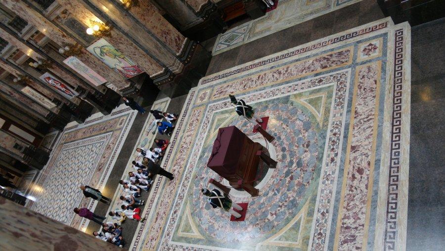06 In het midden de grondwet in een vitrine, aan beide zijde een wachter. Een groep schoolkinderen krijgt rondleiding en uitleg