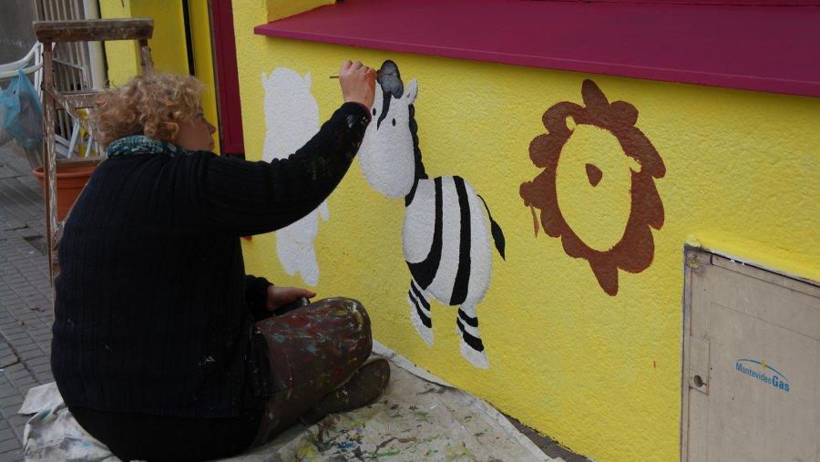 01Schilderes decoreert haar winkelmuur