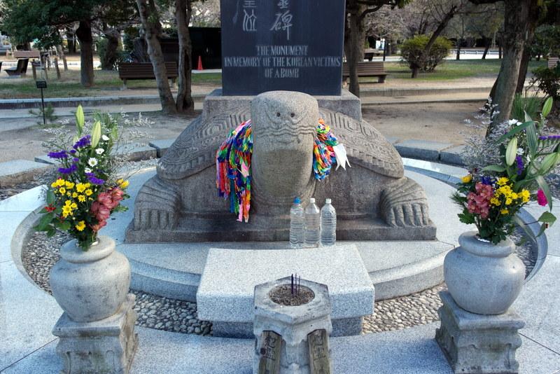 34-bloemen-wierook-kraanvogels-en-flessen-water-bij-monument