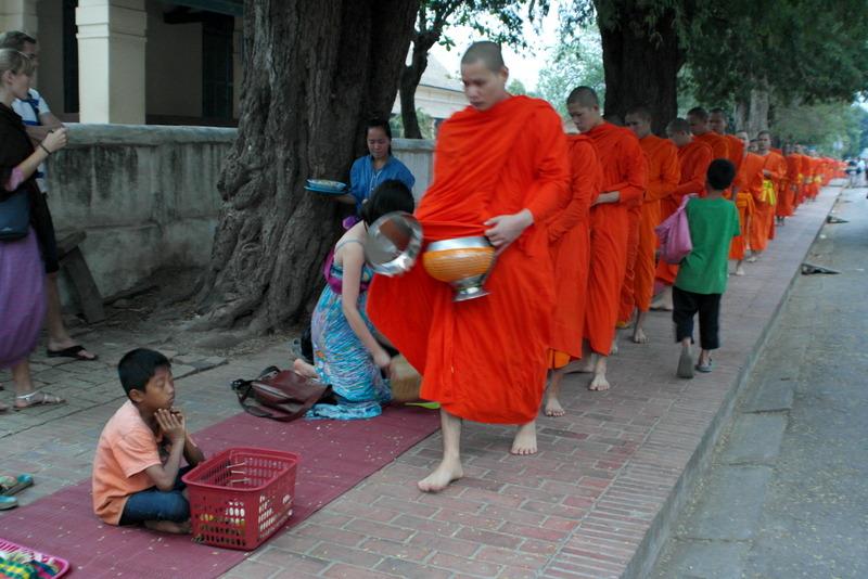 15-enkele-arme-kinderen-zitten-tussen-de-rij-met-hun-mandje-voor-zich-en-krijgen-op-hun-beurt-een-bijdrage-van-de-monniken