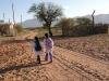 11 kinderen op weg naar hun schooltje, ingang links van de weg