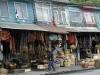 01 Angelmo met haar kleurrijke winkeltjes aan de kade. Verkoper hangt zijn koopwaar op, een nieuwe voorraad gedroogde zeevruchten