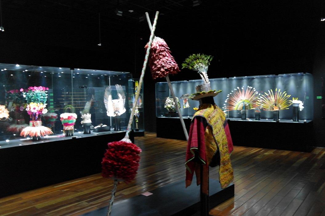 09 zaal waarin presentatie traditionele kleding, voornamelijk gemaakt van veren, veren in talrijke kleuren en maten zeer kunstig en creatief met elkaar verweven en verbonden