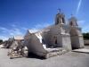 27 Het kerkje binnen de buitenmuur, een typische Altiplanokerk, voorzien van twee torentjes met klokken en een compact schip met dikke muren van adobe