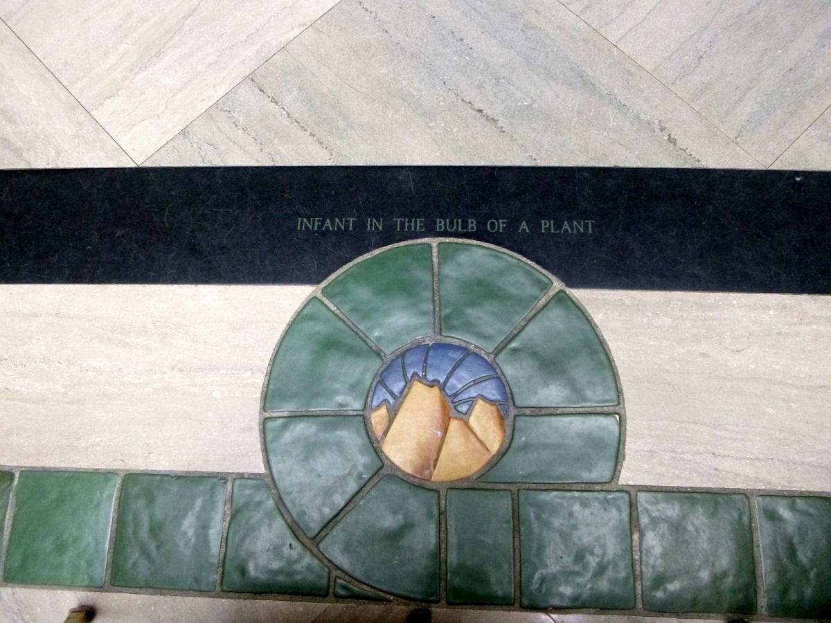 24 uitleg van details van de muurschilderingen rondom beschreven in de historische tegelvloer, de muurschildering begint aan de oostwand Infant in the bulb of a plant