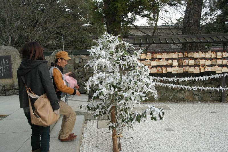 05-jong-gezin-bij-boom-behangen-met-wens-en-geluks-kaartjes
